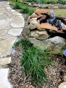 Recycled stone and upcycled pond bush garden
